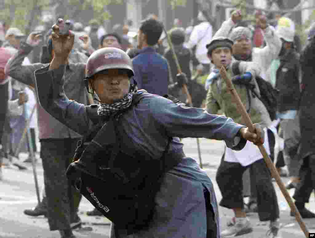 A Muslim man throws rock at police during a protest against an anti-Islam film outside the U.S. Embassy in Jakarta, Indonesia, Sept. 17, 2012.