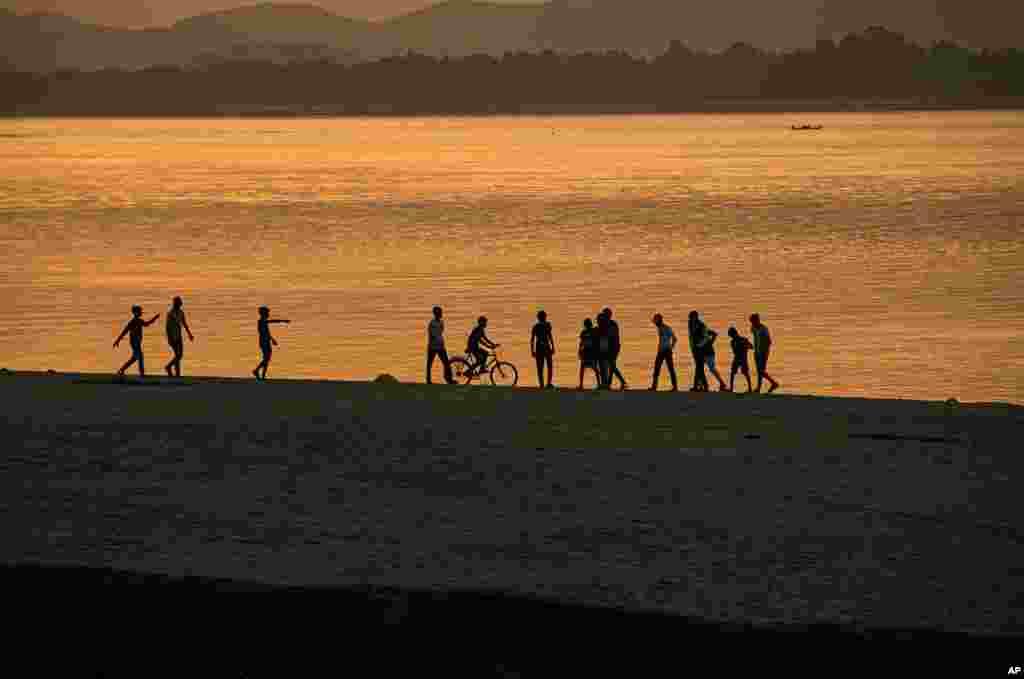 Boys play along the river Brahmaputra as the sun sets in Gauhati, India.