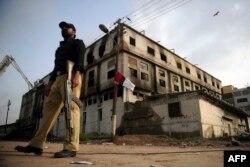 کراچی کے علاقے بلدیہ ٹاون کی گارمنٹ فیکٹری کے باہر ایک پولیس اہلکار مستعد کھڑا ہے۔ اس فیکٹری میں آگ سے جھلس کر کئی افراد ہلاک ہوئے تھے۔