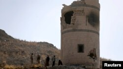 Houthi fighters stand near a damaged guard post at a Presidential Guards barracks they took over on a mountain overlooking the Presidential Palace in Sanaa, Jan. 20, 2015.