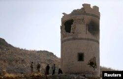 Các chiến binh Houthi đứng gần một chốt canh gác đã bị phá hủy ở một doanh trại tổng thống trên núi mà họ đã giành quyền kiểm soát, nhìn xuống Dinh Tổng thống ở Sanaa, 20/1/2015.