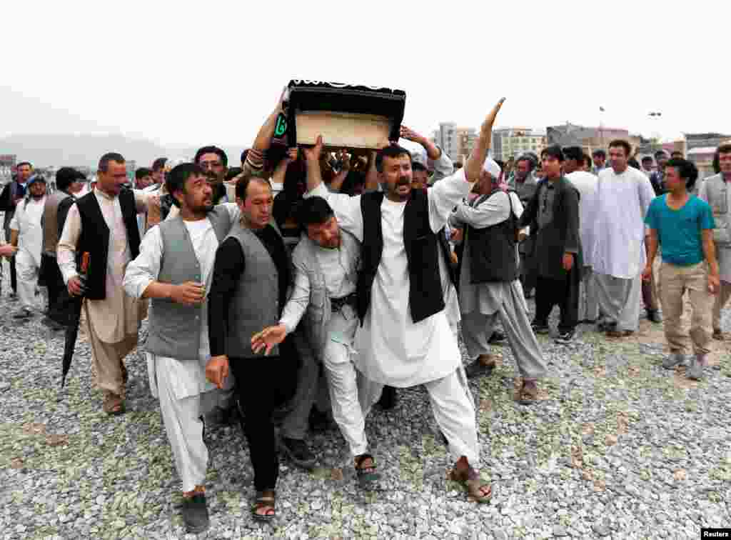 Men carry the coffin of a victim a day after a suicide attack in Kabul, Afghanistan.