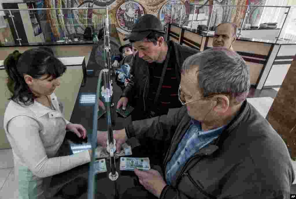 Crimean retirees line up to get their pensions in Russian rubles inside a post office in Simferopol, Crimea, March 25, 2014.
