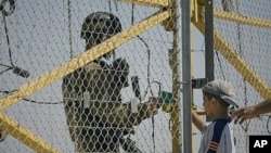 An Israeli soldier checks the identity documents of a Palestinian boy and his father as they wait to cross to their farmland, located behind a section of Israel's separation barrier between the Jewish settlement of Modiin Illit near Ramallah, June 23, 201