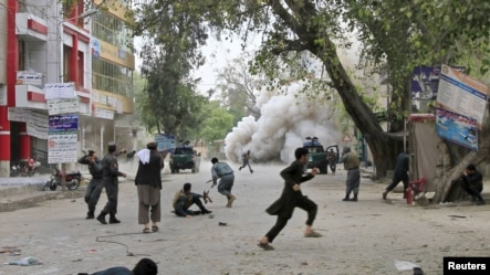 People run for cover after an explosion in Jalalabad, April 18, 2015.
