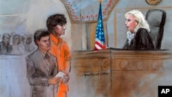 FILE - This courtroom sketch depicts Boston Marathon bombing suspect Dzhokhar Tsarnaev standing with his lawyer Judy Clarke (L) before Magistrate Judge Marianne Bowler (R) during his arraignment in federal court in Boston, July 10, 2013.