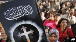 Un homme brandit une Bible lors d'une manifestation dans le sud du Caire, Egypte, 7 mars 2011.