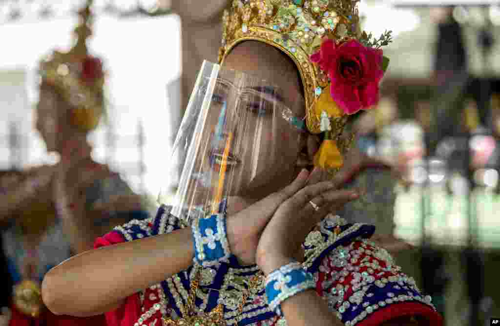 A Thai classical dancer wearing face shield to help curb the spread of the coronavirus performs at the Erawan Shrine in Bangkok, Thailand.