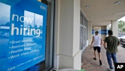 Potrošači ulaze u prodavnicu na Floridi u čijem izlogu stoji oglas da se traže radnici