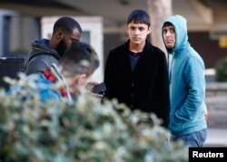 FILE - Two members a group of unaccompanied minors (R and 2nd R) from the Jungle migrant camp in Calais stand outside an immigration centre after being processed after their arrival in Britain, in Croydon, south London, Oct. 18, 2016.