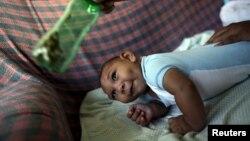 Jackeline, 26 ans, utilise une bouteille verte pour stimuler son fils Daniel, 4 mois, né avec une microcéphalie à Olinda, près de Recife, au Brésil, le 11 février 2016.