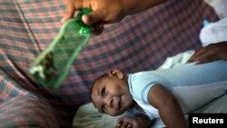 Jackeline, de 26 años, usa una botella verde para estimular a su hijo Daniel, de cuatro meses, quien nació con microcefalia, en Olinda, cerca de Recife, Brasil.