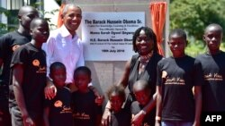 Former US President, Barack Obama (2L) poses for a photograph with local young beneficiaries on July 16, 2018 during the opening of the Sauti Kuu Resource Centre, founded by his half-sister, Auma Obama (3R) at Kogelo in Siaya county, western Kenya.
