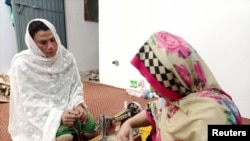 Rani Khan, a transgender woman who teaches the Koran at Pakistan's first transgender only madrasa or a religious school, looks at one of her students during a tailoring lesson in Islamabad, Pakistan March 10, 2021. Picture taken March 10, 2021. REUTERS/Sa