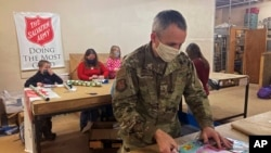 Chief Master Sgt. Winfield Hinkley Jr., Command Senior Enlisted Leader of the Alaska National Guard, wraps a gift in Anchorage, Alaska, that will be sent to a child in one of three rural Alaska villages, on Nov. 17, 2020.