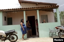 Adilma de Oliveira, 29, who is eight months pregnant, stands in front of her house in Congo, Brazil, Feb. 16, 2016.