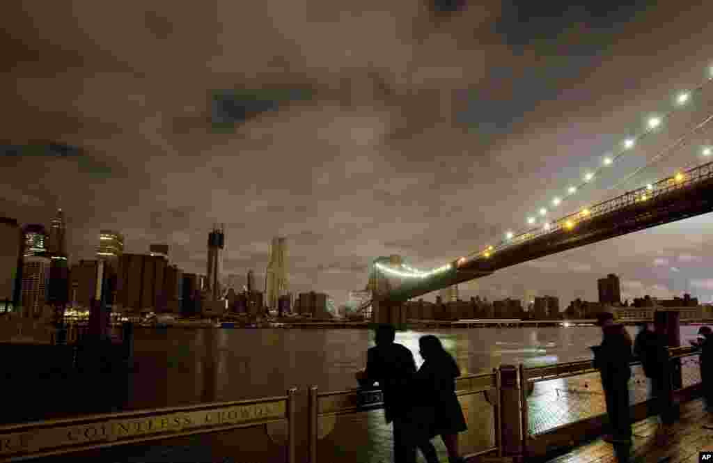People stop along the Brooklyn waterfront to look at the Brooklyn Bridge and the Manhattan skyline, Oct. 30, 2012 in New York.