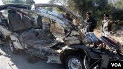 Warga setempat memandangi salah satu kendaraan yang hancur akibat ledakan bom di Hangu, Pakistan.