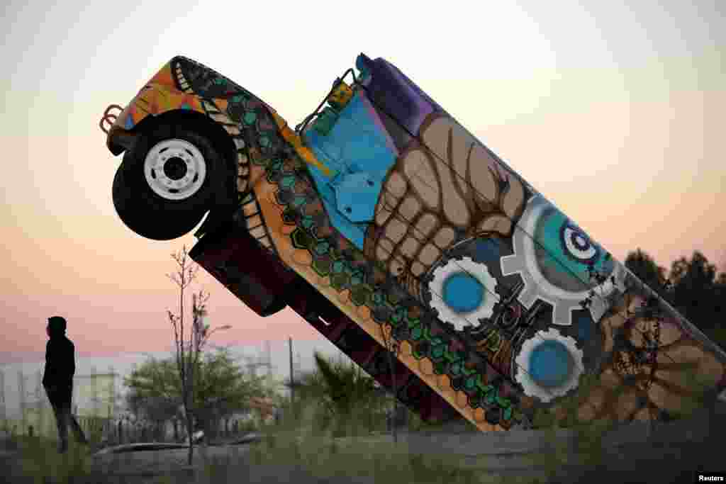 A man stands next to the 'Ser Fronterizo' monument, a retired U.S. school bus cut in half and erected to recognize the employees of assembly factories who use public transportation daily to get to work, in Ciudad Juarez, Mexico, March 14, 2019.