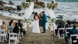 This photo shows bride Namisha Balagopal and groom Suhaas Prasad getting married in a small legal ceremony Aug. 15, 2020, on Muir Beach near San Francisco. The couple plans a larger traditional South Asian Indian wedding this August in Utah. (Vellora Productions via AP)
