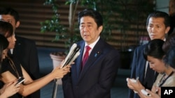 FILE - Japan's Prime Minister Shinzo Abe, center, speaks to reporters at his official residence in Tokyo, July 17, 2015.