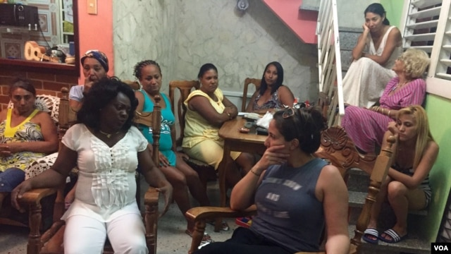 VOA's Victoria Macchi, right foregound, speaks to Damas de Blanco leader Berta Soler, left foreground, in Havana, March 20, 2016.