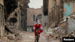 An Iraqi woman, dressed as Santa claus, rides her bicycle, amid the spread of the coronavirus disease (COVID-19), in the old city of Mosul, Iraq, December 18, 2020. Picture taken December 18, 2020. REUTERS/Abdullah Rashid