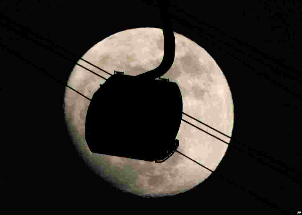 A gondola used to transport people to the biathlon and and cross country skiing venues is silhouetted against the rising moon in Krasnaya Polyana, Russia.
