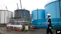 Một công nhân đi qua các bồn chứa nước nhiễm phóng xạ tại nhà máy điện hạt nhân Fukushima Dai-ichi của công ty Điện lực Tokyo bị sóng thần gây hư hại (ảnh tư liệu ngày 23/2/2017).