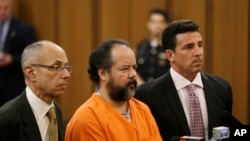 Ariel Castro, center, stands with defense attorneys during arraignment on 977-count indictment, Cleveland, July 17, 2013.