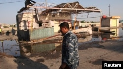 A policeman walks near the site of a bomb attack in Amara, 300 kilometers southeast of Baghdad, Iraq, Aug. 21, 2013.