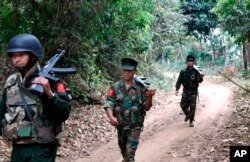 FILE - Kachin Independence Army fighters walk in a jungle path from Mu Du front line to Hpalap outpost in an area controlled by the Kachin rebels in northern Kachin state, Myanmar, March 17, 2018.