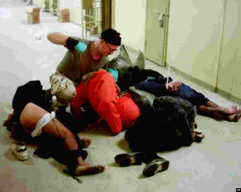 This image obtained by The Associated Press shows Cpl. Charles A. Graner Jr. appearing to punch one of several handcuffed detainees lying on the floor in late 2003 at the Abu Ghraib prison in Baghdad, Iraq.