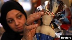 Seorang perempuan menghias permen berbentuk boneka di sebuah pasar menjelang Maulid Nabi Muhammad SAW, di Kairo, Mesir, 12 November 2018.