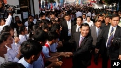 Cambodian Prime Minister and President of Cambodian People's Party Hun Sen, second right in front, greets his supporters after an event by his ruling party to mark the 37th anniversary of the 1979 downfall of the Khmer Rouge regime at the party headquarters in Phnom Penh, Cambodia, Thursday, Jan. 7, 2016. (AP Photo/Heng Sinith)