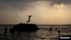 FILE - A boy prepares to jump off a rock into the waters of the Osman Sagar Lake near the southern Indian city of Hyderabad, May 29, 2011.