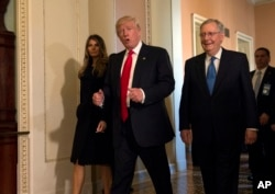 FILE - President-elect Donald Trump, accompanied by his wife, Melania, and Senate Majority Leader Mitch McConnell of Ky., gestures while walking on Capitol Hill in Washington, Nov. 10, 2016.