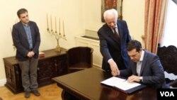 ນາຍົກລັດຖະມົນຕີ ກຣິສ ທ່ານ Alexis Tsipras, ຂວາ, ກຳລັງ ເຊັນເອກກະສານການເງິນ ໃນຂະນະທີ່ ລັດຖະມົນຕີ ການເງິນ ຄົນຂ້າມ ທ່ານ Euclid Tsakalotos, ຊ້າຍ, ຢຶນເບິ່ງຢູ່ຂ້າງ.