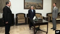 Nawaf Fares, left, is sworn in as Syria's ambassador to Iraq before President Bashar al-Assad, right, and Foreign Minister Walid Moallem in Damascus, September 16, 2008.