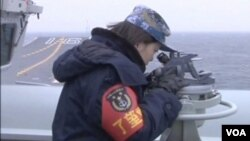 中國遼寧號航空母艦星期四駛過台灣海峽,一名女官兵視察海面情況。。(視頻截圖)