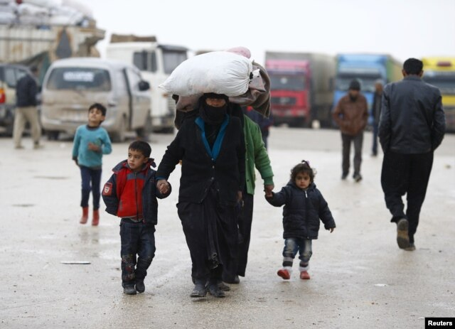 FILE - Internally displaced Syrians carry their belongings as they arrive at a refugee camp near the Bab al-Salam crossing, across from Turkey's Kilis province, on the outskirts of the northern border town of Azaz, Syria, Feb. 6, 2016.