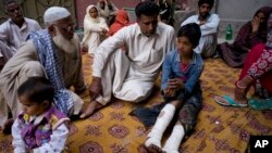 Fahd Ali, 10, right, who was injured in a bombing that killed his parents and sister and wounded two sisters, narrates his ordeal to visitors outside his home in Lahore, Pakistan, Monday, March 28, 2016. Pakistan's prime minister on Monday vowed to eliminate perpetrators of terror attacks such as the massive suicide bombing that targeted Christians gathered for Easter the previous day in the eastern city of Lahore, killing 70 people. (AP Photo/B.K. Bangash)