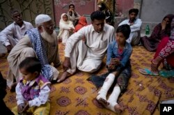 Fahd Ali, 10, right, who was injured in a bombing that killed his parents and sister and wounded two sisters, narrates his ordeal to visitors outside his home in Lahore, Pakistan, March 28, 2016.