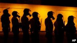 警察在对弗格森镇示威群众使用催泪瓦斯后准备前进。