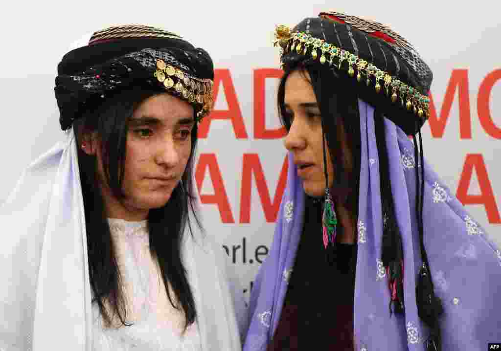 Nadia Murad (R) and Lamia Haji Bashar, public advocates for the Yazidi community in Iraq and survivors of sexual enslavement by the Islamic State jihadists react after being awarded laureates of the 2016 Sakharov human rights prize, at the European parliament in Strasbourg, France.