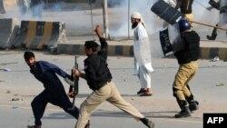 پشاور میں ایک مظاہرے کے دوران پولیس احتجاج کرنے والوں کو منتشر کر رہی ہے۔