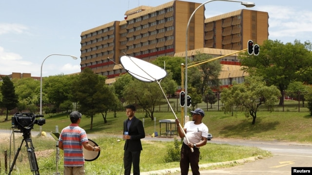 A television crew films outside a military hospital where former South African president Nelson Mandela is hospitalized in Pretoria, December 9, 2012.