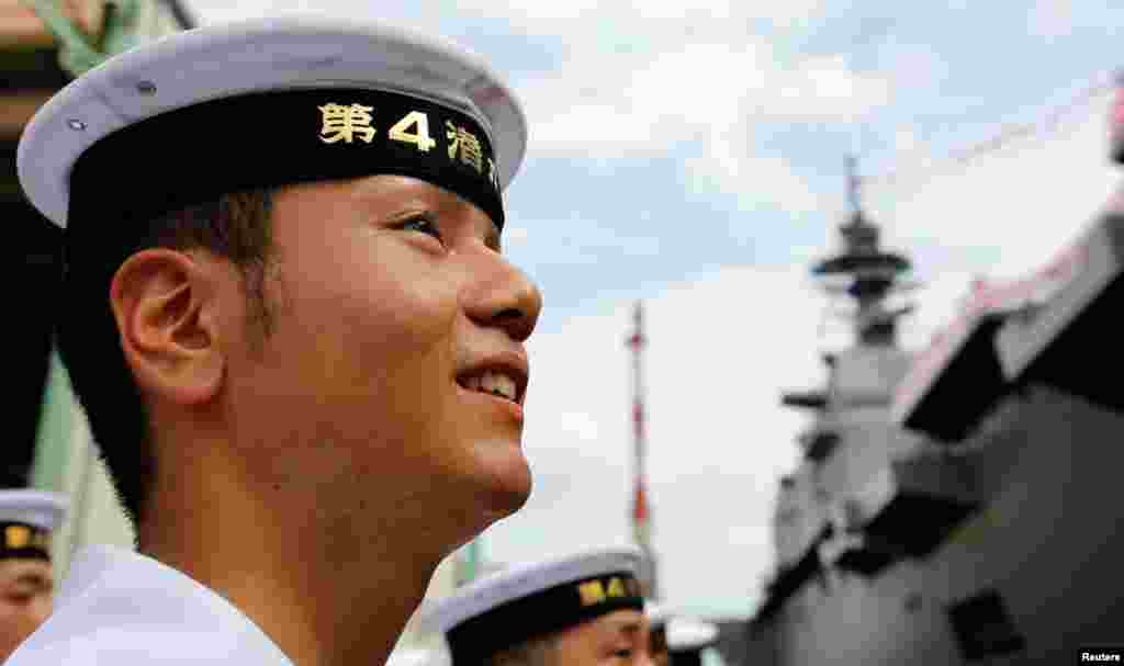 A member of Japan's Maritime Self-Defense Force looks at the DDH183 Izumo, August 6, 2013.