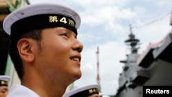 FILE - A member of Japan's Maritime Self-Defense Force looks at its new helicopter destroyer DDH183 Izumo, the largest surface combatants of the Japanese navy, before its launching ceremony in Yokohama, south of Tokyo, Aug. 6, 2013.