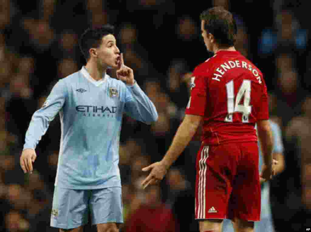 Manchester City's Samir Nasri (L) gestures to Liverpool's Jordan Henderson during their English League Cup semi-final, first leg soccer match at the Etihad Stadium in Manchester, northern England, January 11, 2012.